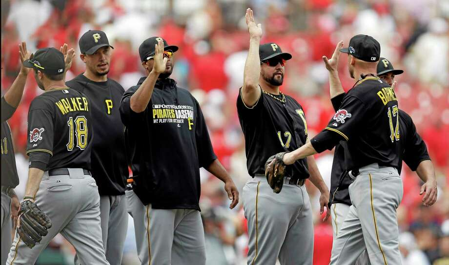 Pittsburgh Pirates players, including Neil Walker (18) and Clint Barmes (12) celebrate after beating the St. Louis Cardinals 7-1 in Game 2 of the National League division series on Friday in St. Louis. The best-of-five games series is tied at 1. Photo: Jeff Roberson — The Associated Press   / AP