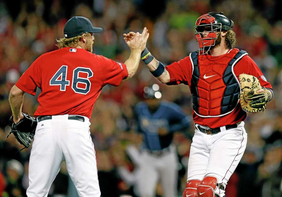 Red Sox pitcher Ryan Dempster (46) and catcher Jarrod Saltalamacchia celebrate a 12-2 win over the Tampa Bay Rays in Game 1 of the American League division series Friday in Boston. Photo: Michael Dwyer — The Associated Press   / AP
