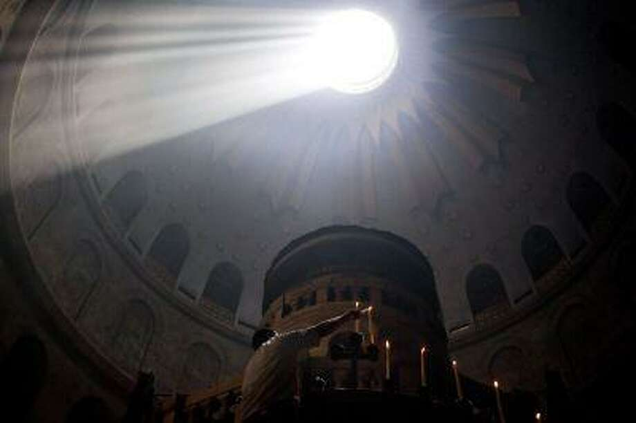 A worker lights candles at the Church of the Holy Sepulchre, traditionally believed to be the burial site of Jesus Christ, in Jerusalem's Old City, Sunday, May 5, 2013. (AP Photo/Sebastian Scheiner) Photo: AP / AP