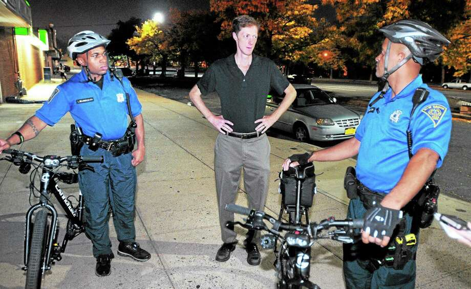 (Arnold Gold — New Haven Register)  New Haven Police Officers Les Billingslea (left) and Todd Kelley (right) talk with mayoral candidate Justin Elicker (center) on their beat near the New Haven Police Dept. Substation on Charles St. in New Haven on 10/2/2013. Photo: Journal Register Co.