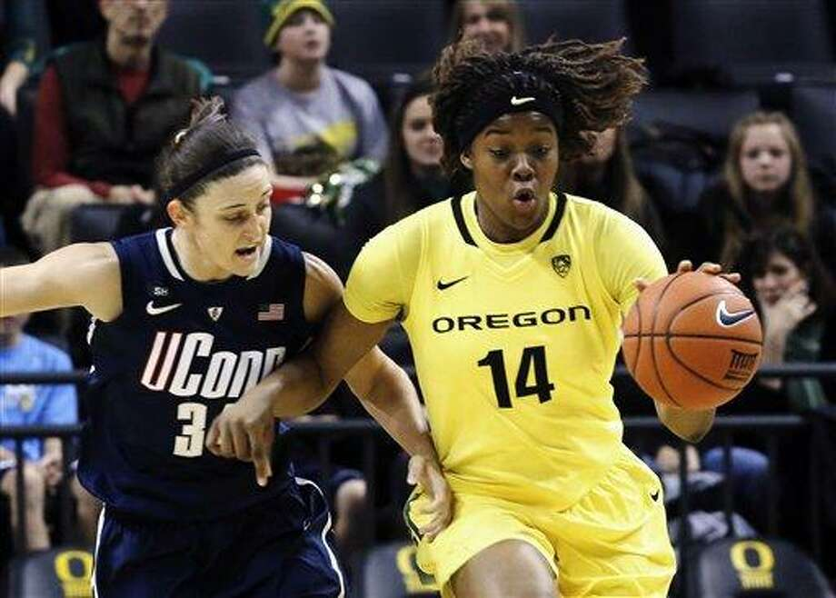 Oregon forward Jillian Alleyne, right, races downcourt as Connecticut guard Kelly Faris defends during the first half of an NCAA college basketball game in Eugene, Ore., Monday, Dec. 31, 2012.(AP Photo/Don Ryan) Photo: AP / AP