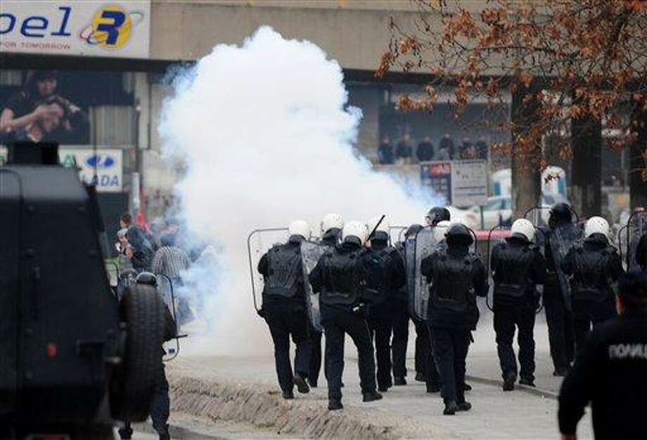 The police use tear gas as a group of ethnic Albanians throw stones at them, during a violent protest of a group of ethnic Albanians in Skopje, Macedonia, Saturday, March 2, 2013. Hundreds of ethnic Albanians staged a contra-protest on Saturday to express support for the designation of the new defense minister. Police said Saturday at least 20 people, from whom 13 police officers and other mainly youngsters were injured in a series of scuffles that erupted late on Friday and continued over night when a group of a few hundred Macedonians started a protest against the designation of a new defense minister Talat Xhaferi, an ethnic Albanian and former rebel commander. (AP Photo/Vangel Tanurovski) Photo: AP / AP