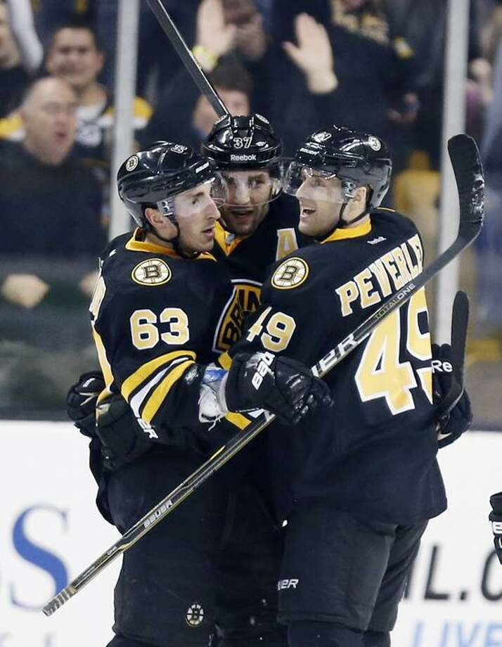 Boston Bruins' Brad Marchand (63) celebrates his go-ahead goal with teammates Patrice Bergeron (37) and Rich Peverley (49) during the third period of an NHL hockey game against the Tampa Bay Lightning in Boston, Saturday, March, 2, 2013. The Bruins won 3-2. (AP Photo/Michael Dwyer) Photo: AP / AP
