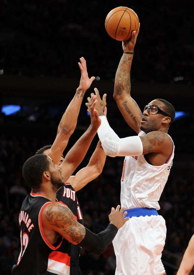 New York Knicks' Amare Stoudemire, right, shoots over Portland Trail Blazers' LaMarcus Aldridge and Jared Jeffries, rear, during the first quarter of an NBA basketball game, Tuesday, Jan. 1, 2013, at Madison Square Garden in New York. (AP Photo/Bill Kostroun) Photo: AP / AP2013