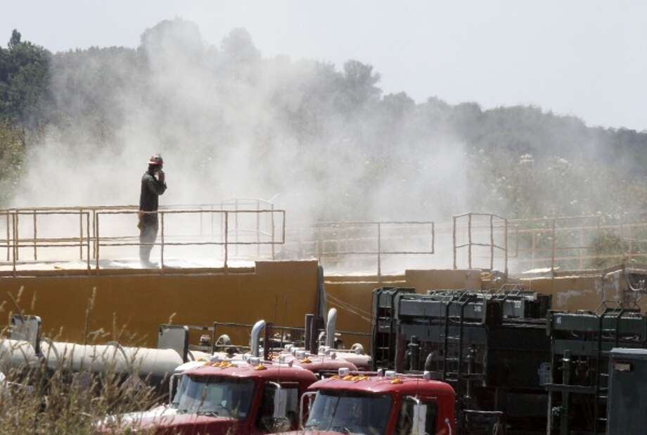 A worker at the Marcellus Shale Layer stands on top of a storage bin as the dust from the hydraulic fracking process billows around him. Disposal of waste from fracking has contaminated nearby water sources, according to a new study. Photo: AP / 2011 AP