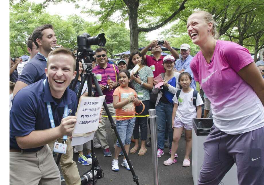 Melanie Stengel -- Register      New Haven Open-Jeff Watson (L) laughs with tennis player, Petra Kvitova, as they play a guessing game about her fellow players 08/15.  This followed a round table discussion with the press.