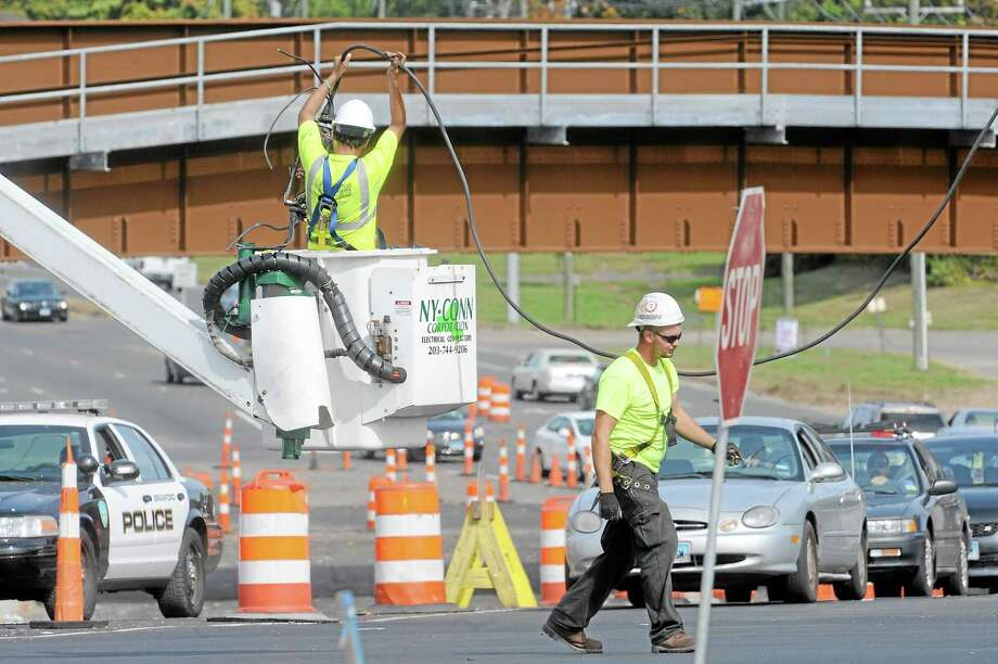 (VM Williams/ New Haven Register) NY-Conn Corp. electrical worker holds a cable above his head on Route 1 at the intersection of Short Beach in Branford Thursday. Work on the light has closed the intersection. Photo: Journal Register Co.
