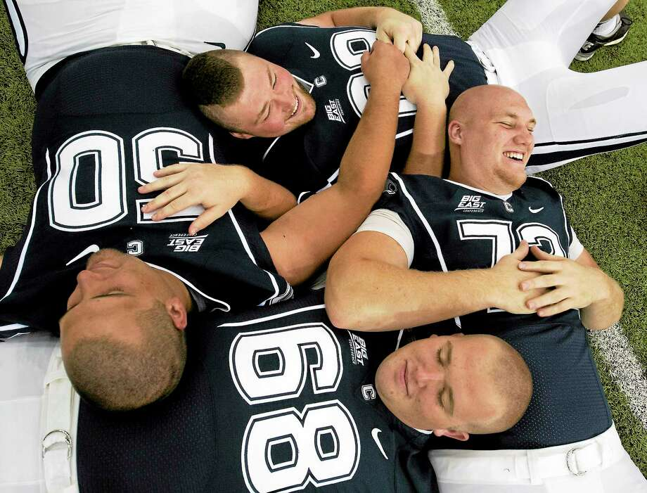 Clockwise from left, UConn linemen Tyler Bullock (50), Steve Greene, Jimmy Bennett and Bryan Paull (68) relax during media day in Storrs back in August. Saturday will mark the final collegiate games for Bullock, Greene and Bennett. Photo: Jessica Hill — The Associated Press   / A2012