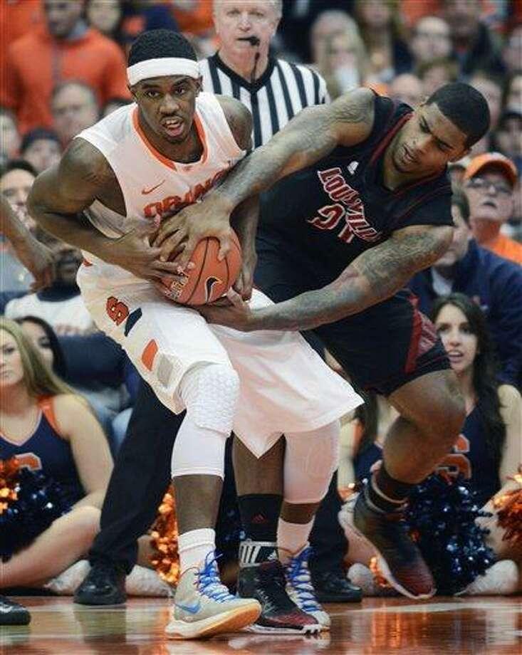 AP Photo/Kevin Rivoli Syracuse's C. J. Fair, left, battles Louisville's Chane Behanan for a loose ball during the first half of an NCAA college basketball game in Syracuse, N.Y., Saturday, March 2, 2013. Photo: AP / FR60349 AP