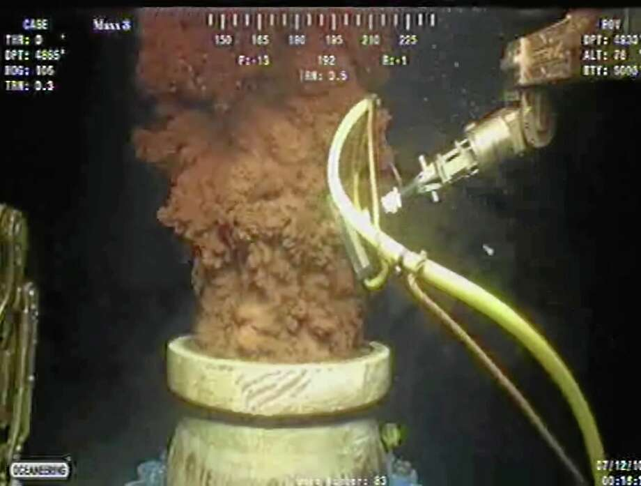 FILE - In this Monday July 12, 2010 image from video made available by BP PLC, oil flows out of the top of the transition spool, which was placed into the gushing wellhead and will house the new containment cap, at the site of the Deepwater Horizon oil spill in the Gulf of Mexico. The federal trial over the 2010 BP oil spill resumed Monday, Sept. 30, 2013, with a focus on the company's response to the disaster, with millions of dollars at stake as the two sides argue over how much oil spewed into the Gulf of Mexico. (AP Photo/BP PLC, File) Photo: AP / BP PLC