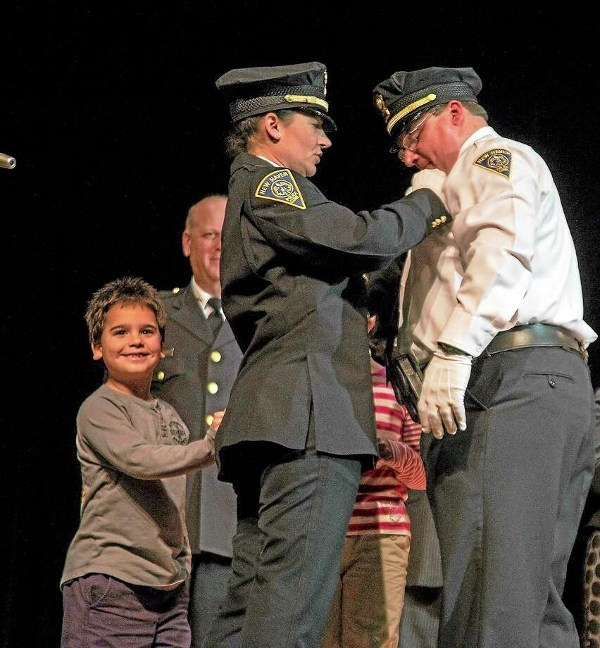 Danny Johnson, 8, beams as his mother, New Haven police Lt. Julie Johnson, pins a badge on Lt. Herb Johnson during Friday night's New Haven police promotion ceremony. Photo: Rich Scinto — New Haven Register