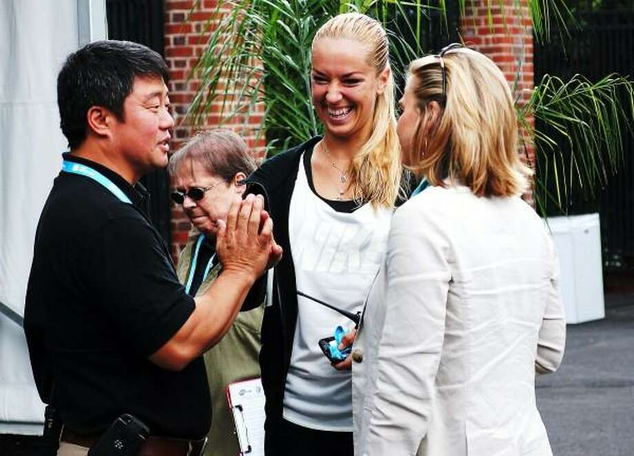 """Peter Casolino â?? RegisterWTA Tour supervisor Tony Cho high-fives tennis pro Sabine Lisicki along with Ann Worcester before the Draw ceremony at the New Haven Open at Yale.<a href=""""mailto:pcasolino@newhavenregister.com"""">pcasolino@newhavenregister.com</a>"""