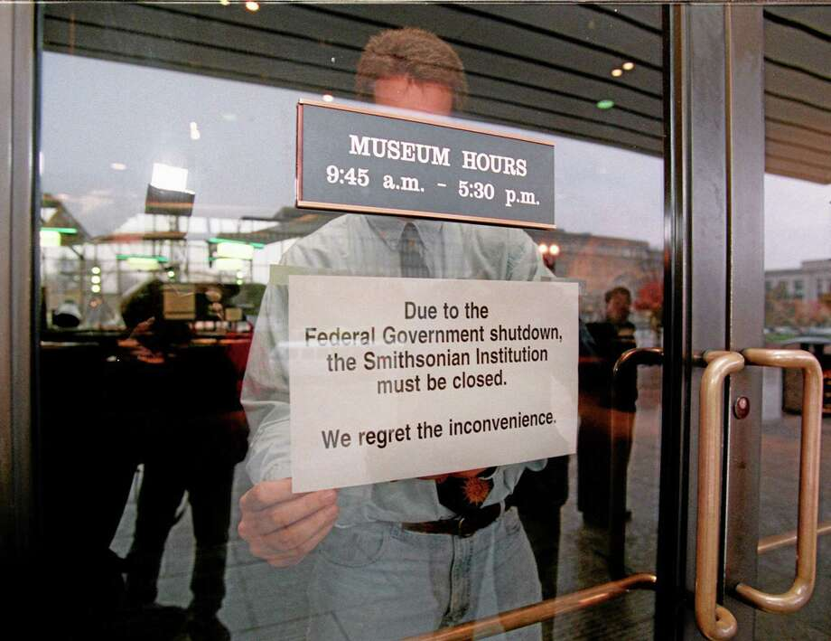 FILE - In this Nov. 14, 1995, file photo, Mike Fetters afixes a closed sign on a door at the Smithsonian's Air and Space Museum in Washington as parts of the federal government were shutdown due a federal budget impasse between President Clinton and the Republican Congress. Moments later, the sign was taken down and the museum opened as all Smithsonian museums in Washington were told from their headquarters to stay open until further notice. OK, gridlocked politicians we're used to. But why padlock the Statue of Liberty? You don't see other democracies shuttering landmarks and sending civil servants home just because their political parties can't get along. The potential for a shutdown is a quirk of American history. So if you're tired of blaming tea party Republicans or President Barack Obama, you can lay some responsibility on the Founding Fathers. Or blame Jimmy Carter. Or Newt Gingrich's temper tantrum. A quick history of government shutdowns, American-style. (AP Photo/Doug Mills, File) Photo: AP / AP