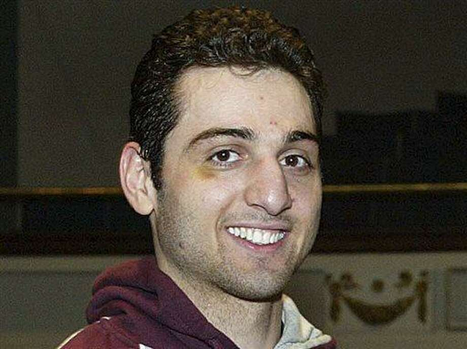 FILE - In this Feb. 17, 2010, photo, Tamerlan Tsarnaev, left, smiles after accepting the trophy for winning the 2010 New England Golden Gloves Championship in Lowell, Mass. Tsarnaev, the older of the brothers suspected in the Boston Marathon bombing, died from gunshot wounds and blunt trauma to his head and torso, his death certificate says. (AP Photo/The Lowell Sun, Julia Malakie, File) MANDATORY CREDIT Photo: AP / The Sun of Lowell