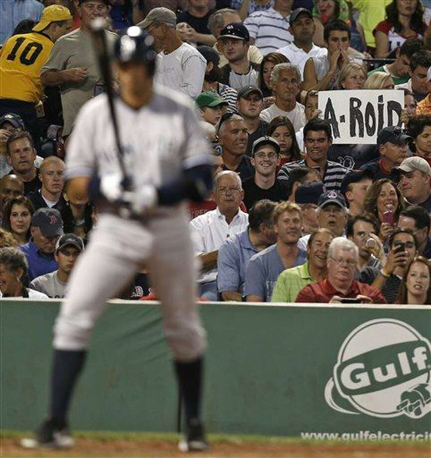 A fan holds up a sign as New York Yankees' Alex Rodriguez comes up to bat during the third inning of a baseball game against the Boston Red Sox at Fenway Park in Boston on Friday, Aug. 16, 2013. (AP Photo/Winslow Townson) Photo: AP / FR170221 AP