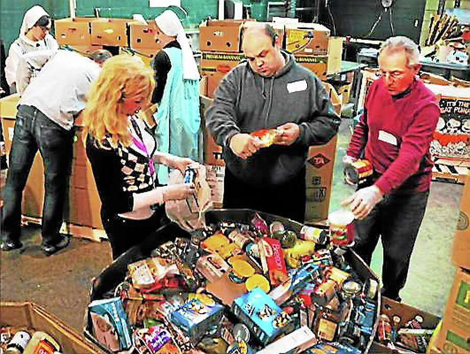 From left, volunteers Kim Lucas and Mark Dalton of West Haven and Al DeFilippo of Branford sort food drive donations at the Connecticut Food Bank headquarters in East Haven. Photo: Peter Hvizdak — New Haven Register File