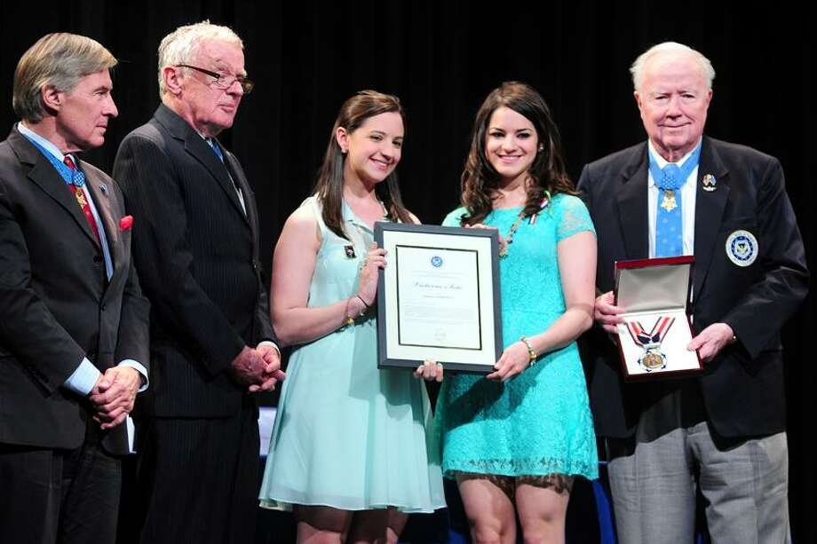 Sisters Jillian (center left) and Carliee Soto (center right) accept the Citizen Honors Medal in honor of their sister, Sandy Hook School teacher Victoria Soto, at a ceremony at Newtown High School on 5/6/2013.  Medal of Honor Recipient presenters Paul Bucha (far left) and Thomas Kelley (left) stand with them for a photograph. At right holding the medal is Medal of Honor Recipient presenter Bruce Crandall.Photo by Arnold Gold/New Haven Register