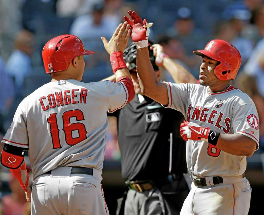 The Angels' Hank Conger, left, congratulates Chris Nelson after Nelson hit an eighth-inning grand slam off Yankees reliever Boone Logan on Thursday. Photo: Kathy Willens — The AssociAted Press   / AP