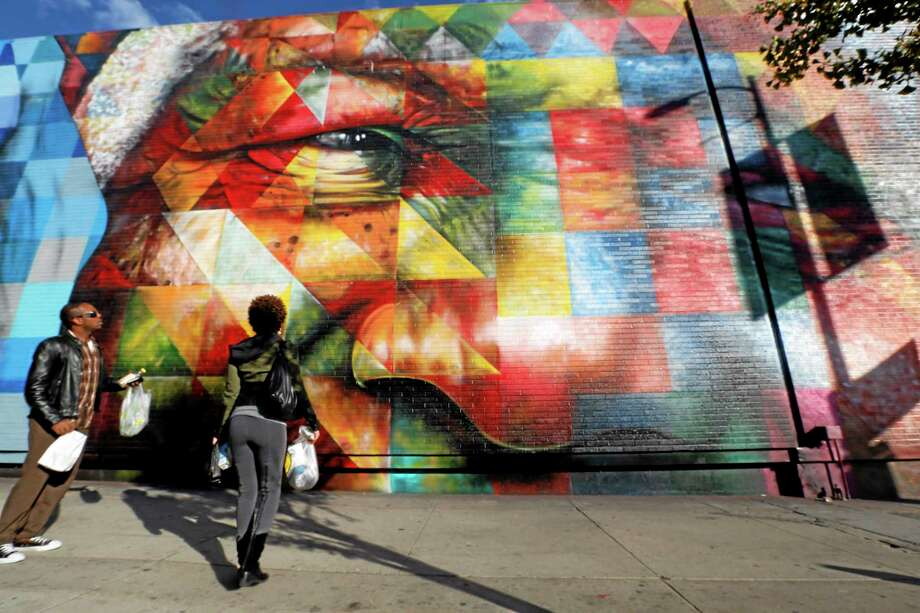 People examine a painting by Brazilian muralist Eduardo Kobra that features the face of Nelson Mandela on a wall on Highland Avenue in the Hollywood district of Los Angeles Thursday. Photo: Reed Saxon — The Associated Press   / AP
