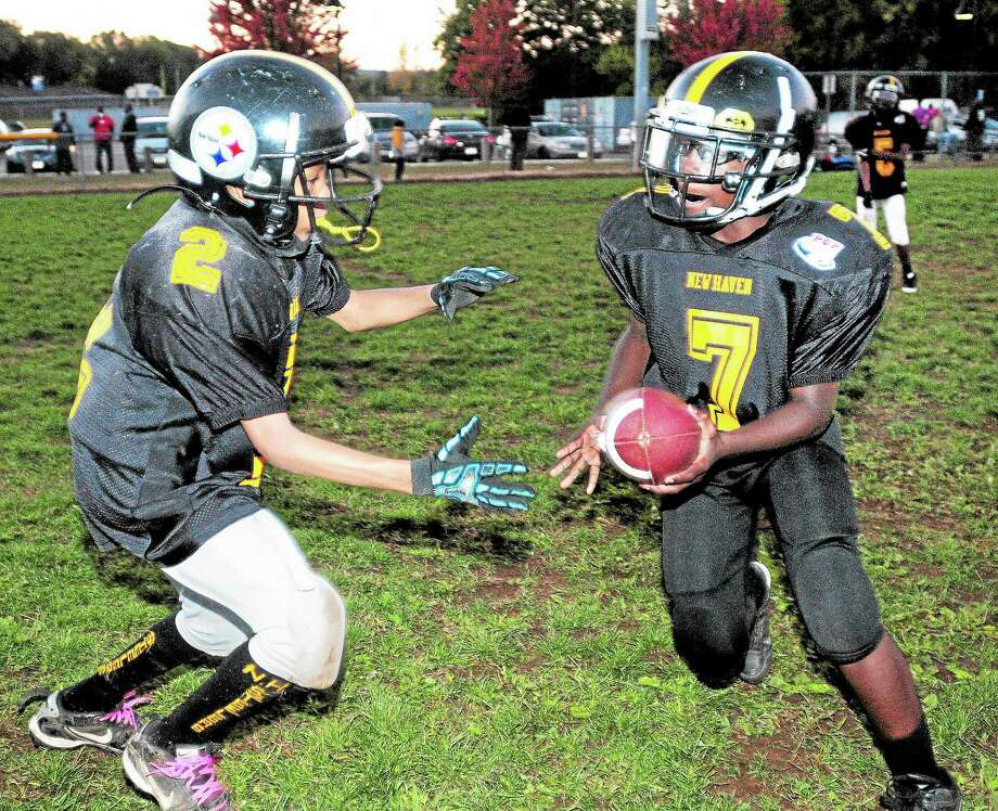 Quarterback Sahim Hasan, right, 11, of the New Haven Steelers hands off to Hessan Lewis, 11, during a recent practice at Bowen Field in New Haven. Photo: Arnold Gold — New Haven Register