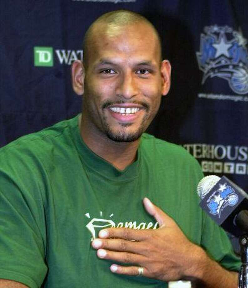 """John Amaechi, the first British player to start in an NBA game, playfully covers a tee shirt that states """"Amaechi Tea Co."""" at a news conference in Orlando, Fla. USA, in this file photo dated Tuesday Aug. 8, 2000. Amaechi became the first openly gay former NBA player with a landmark public statement in 2007, three years after retiring, but in a telephone interview with The Associated Press, Amaechi disclosed that he is in contact with gay English Premier League players to advise them about gay issues. Photo: AP / AP"""