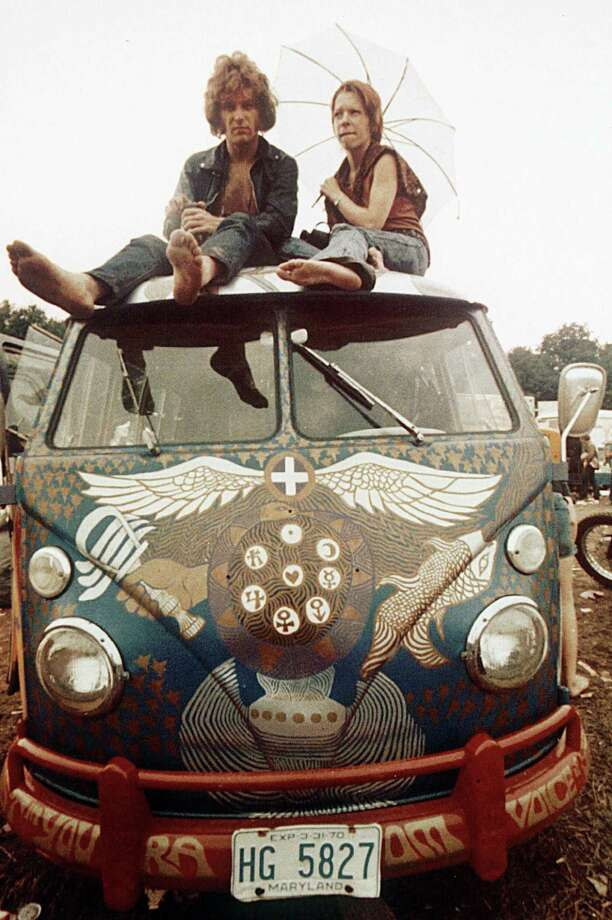 Concert-goers sit on the roof of a Volkswagen bus at the Woodstock Music and Arts Fair at Bethel, N.Y., in mid-August, 1969. The three-day concert attracted hundreds of thousands of people, and became a landmark cultural event of the late '60s. (AP Photo) Photo: AP / 1969 AP