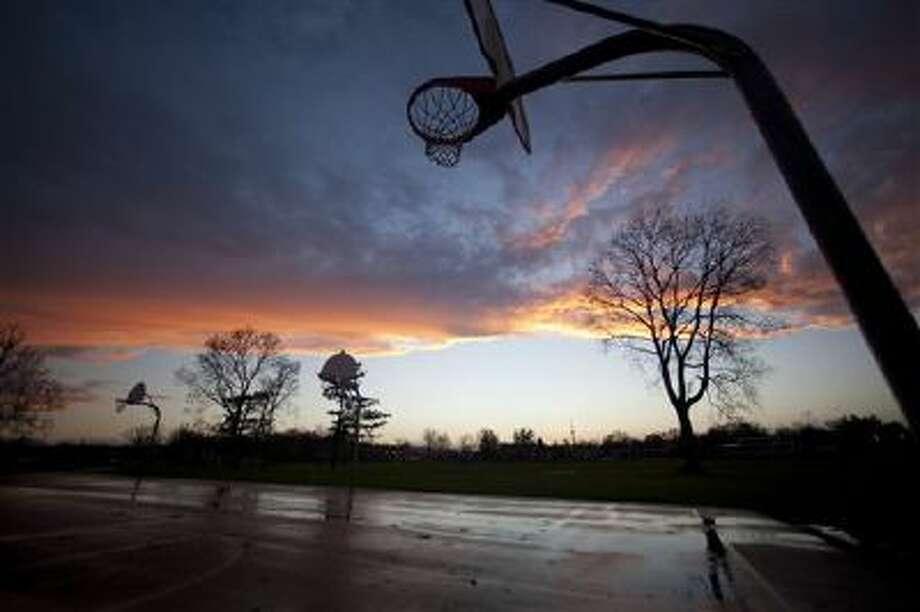 A sunset glows following high winds and storms on this Michigan playground. Photo: AP / Kalamazoo Gazette