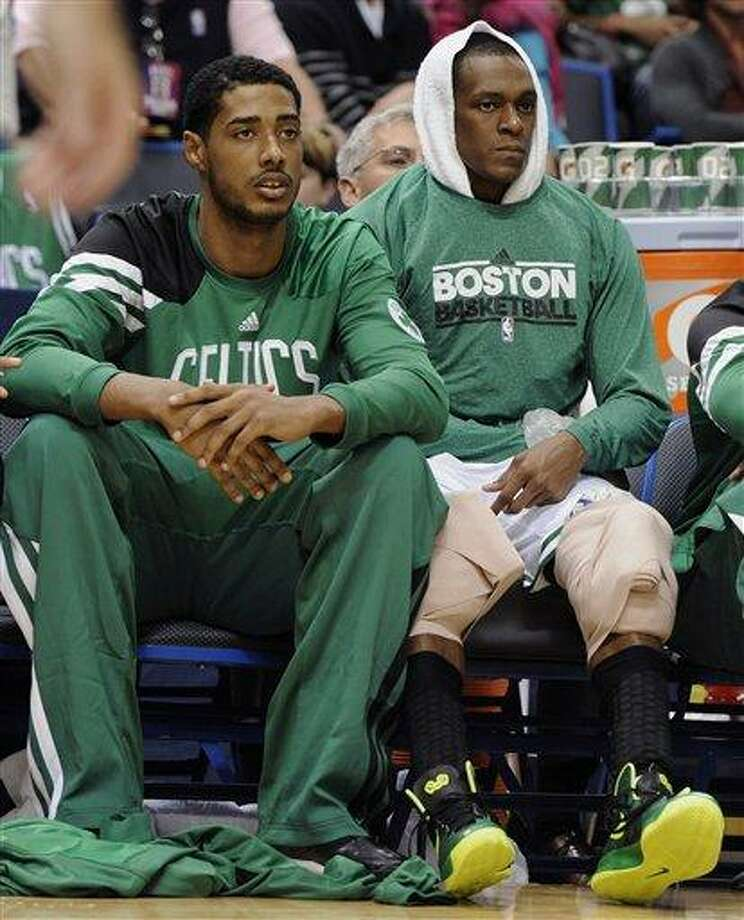 Boston Celtics' Fab Melo, left, and Rajon Rondo, watch play in the second half of an NBA preseason basketball game against the New York Knicks, Saturday, Oct. 13, 2012, in Hartford, Conn. New York won in overtime 98-95. (AP Photo/Jessica Hill) Photo: AP / FR125654 AP