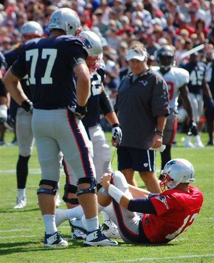 New England Patriots quarterback Tom Brady grabs his left knee after an apparent injury during a joint workout with the Tampa Bay Buccaneers at NFL football training camp, in Foxborough, Mass., Wednesday, Aug. 14, 2013. Watching Brady are Patriots tackle Nate Solder (77) and head coach Bill Belichick. (AP Photo/Will DiTullio) Photo: ASSOCIATED PRESS / AP2013
