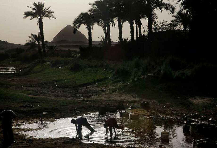 """Egyptian villagers catch lobsters in a pond in front of the historical site of the 4,500-year-old """"bent"""" pyramid, of Pharaoh Sneferu known for its oddly shaped profile, outside the village of Dahshour, 50 miles (80 Kilometers) south of Cairo, Egypt, Monday, April 29, 2013.(AP Photo/Amr Nabil) Photo: ASSOCIATED PRESS / AP2013"""