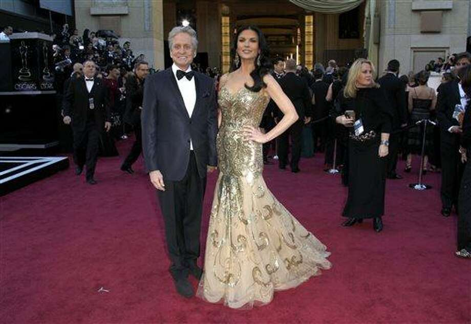 FILE - In this Feb. 24, 2013 file photo, actors Michael Douglas, left, and Catherine Zeta-Jones arrive at the Oscars at the Dolby Theatre, in Los Angeles. According to her publicist on Monday, April 29, 2013, Zeta-Jones has pro-actively checked into a health care facility. Previously, she has said that she is committed to periodic care in order to manage her health in an optimum manner. (Photo by Carlo Allegri/Invision/AP, File) Photo: Carlo Allegri/Invision/AP / Invision