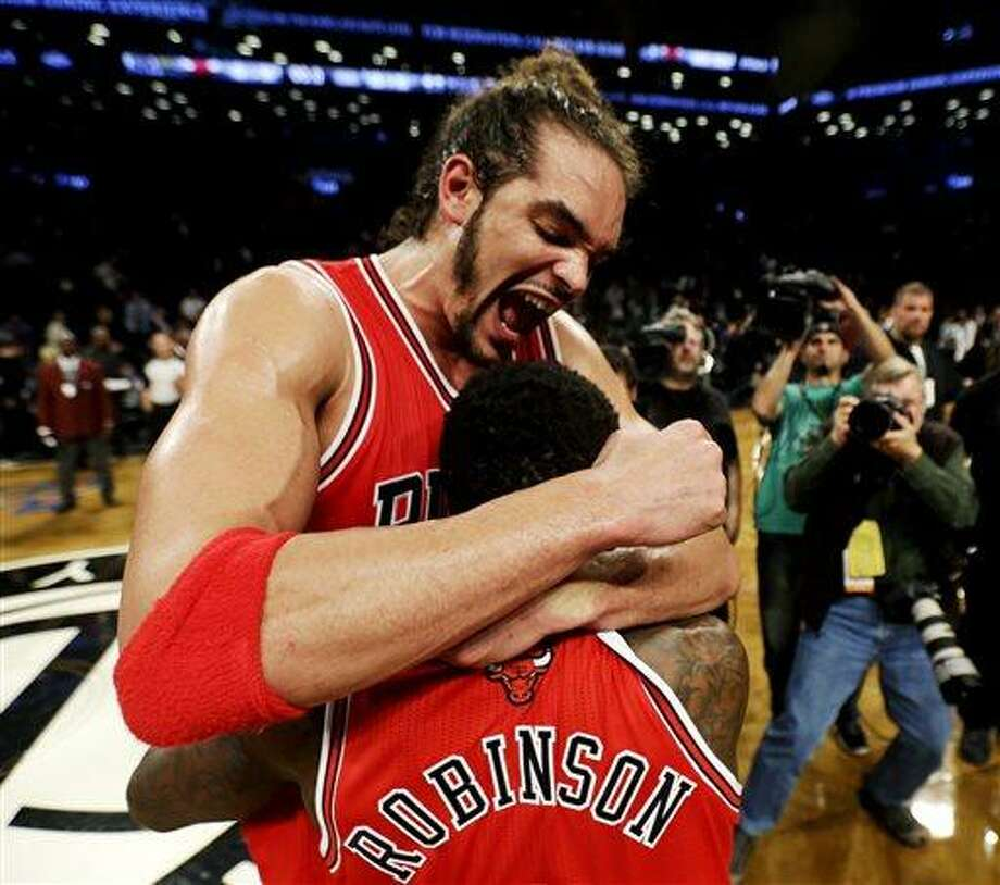 Chicago Bulls' Joakim Noah, top, celebrates with teammate Nate Robinson after defeating the Brooklyn Nets 99-93 in Game 7 of their first-round NBA basketball playoff series in New York, Saturday, May 4, 2013. The Bulls won the series to advance to a second-round series against the Miami Heat beginning Monday. (AP Photo/Julio Cortez) Photo: AP / AP