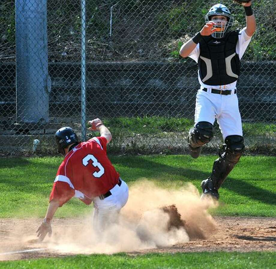 "Hamden--Cheshire's Kevin Mirando slides into home for a run as Hamden catcher #24_________________ jumps for the late throw. The run was due to a passed ball/ Unearned run. Photo-Peter Casolino/Register <a href=""mailto:pcasolino@newhavenregister.com"">pcasolino@newhavenregister.com</a>"