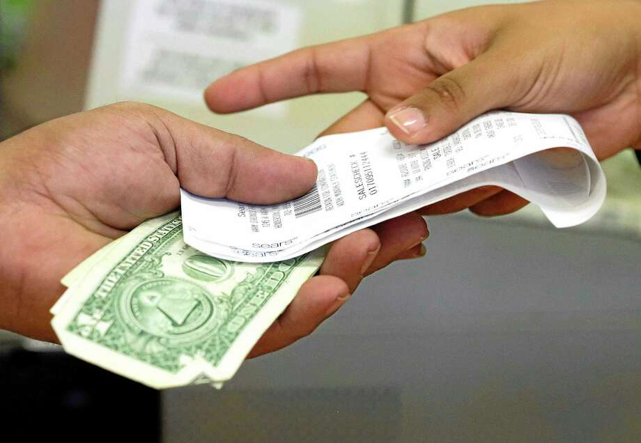 A cashier hands a customer his change and receipt during a transaction at a Sears store, in Henderson, Nev. Photo: Julie Jacobson — The Associated Press   / AP