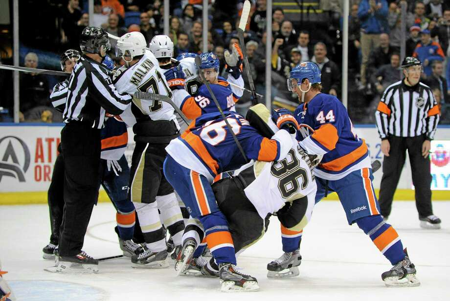 The Penguins' Evgeni Malkin (71), Jussi Jokinen (36) and teammates fight with the Islanders' Peter Regin (16), Calvin de Haan (44) and teammates during the third period of Tuesday's game in Uniondale, N.Y. Pittsburgh beat New York 3-2 in overtime. Photo: Kathy Kmonicek — The Associated Press   / FR170189 AP