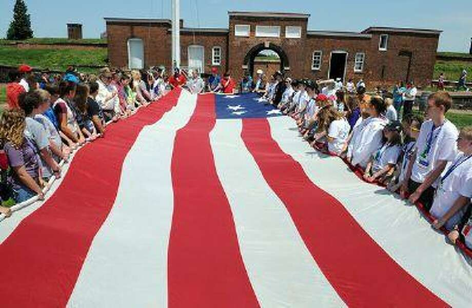 Schoolchildren last year unfurl a 30-by-42-foot replica of the famous Star-Spangled Banner at Fort McHenry in Baltimore. The real thing is on display at the National Museum of American History in Washington. About 200 seamstresses this month are hand-sewing a new flag, just as large as the original, at the Maryland Historical Society in Baltimore. (Photo for The Washington Post by Astrid Riecken) Photo: The Washington Post / THE WASHINGTON POST