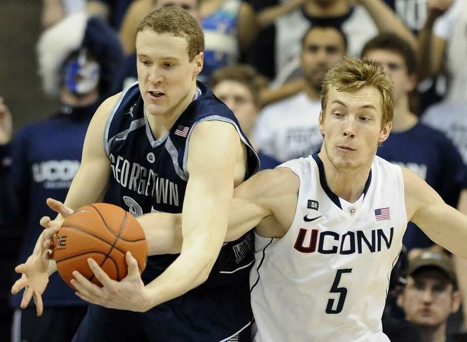 Georgetown's Nate Lubick, left, tangles with Connecticut's Niels Giffey during the first half of an NCAA college basketball game in Storrs, Conn., Wednesday, Feb. 27, 2013. (AP Photo/Jessica Hill) Photo: AP / FR125654 AP