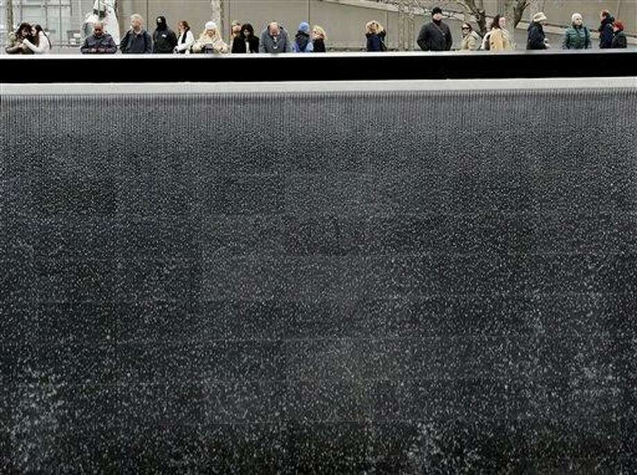 Visitors look over the waterfalls Monday at the National September 11 Memorial and Museum in New York. Associated Press Photo: AP / AP
