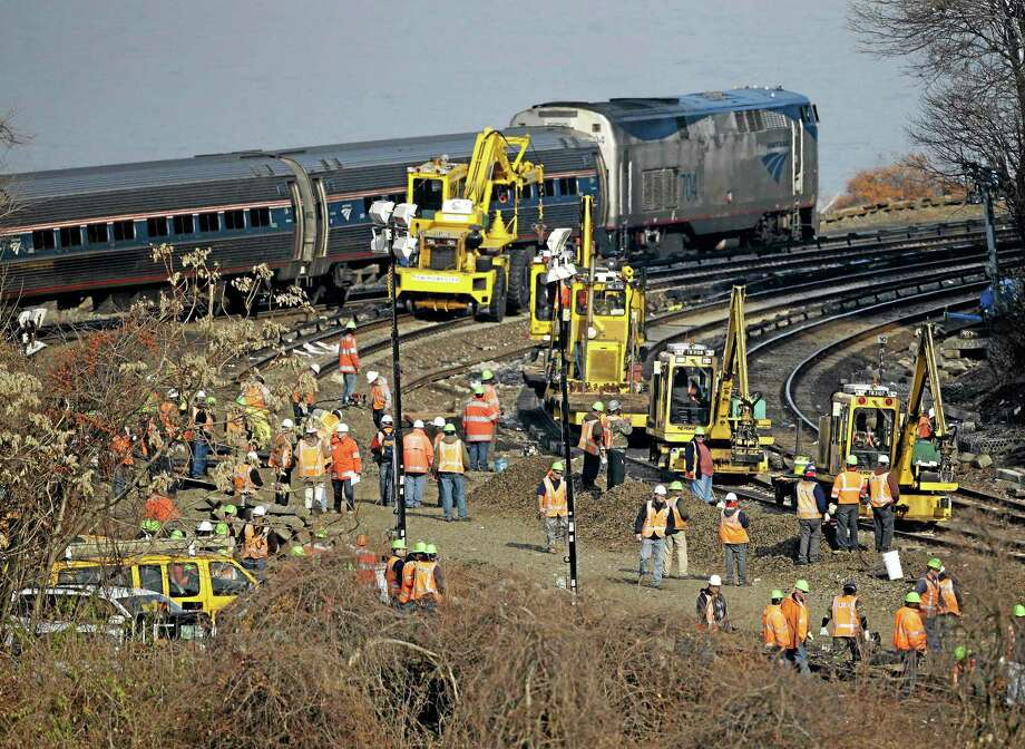 A train passes by the scene of repair efforts at the site of a train derailment in the Bronx borough of New York, Tuesday, Dec. 3, 2013.  The National Transportation Safety Board says right now, it doesn't know whether faulty brakes or human error caused Sunday's derailment of a New York City train that killed four people and injured more than 60. But NTSB member Earl Weener says information from the train's two data recorders shows the train was going 82 mph on a turn when it should have been going no more than 30 mph.  (AP Photo/Seth Wenig) Photo: AP / AP