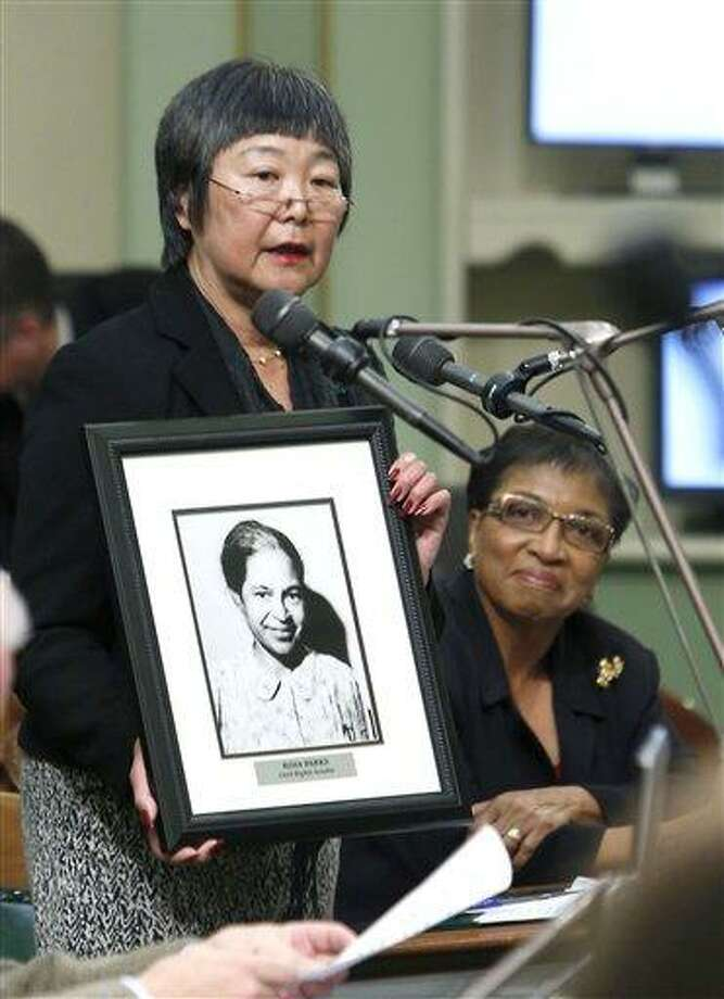 Assemblywoman Mariko Yamada, D-Davis, holds a photo of the late Civil Rights activist Rosa Parks while calling for passage of her Assembly Resolution honoring Parks during Black History Month ceremonies at the Capitol in Sacramento,  Calif., Monday, Feb. 4. 2013. On what would have been her 100th birthday, the Assembly approved the resolution for Parks who became one of the enduring figures of the Civil Rights movement when she refused to cede her seat to a white man on a Montgomery, Ala. bus in 1955.  Parks died in 2005. (AP Photo/Rich Pedroncelli) Photo: AP / AP