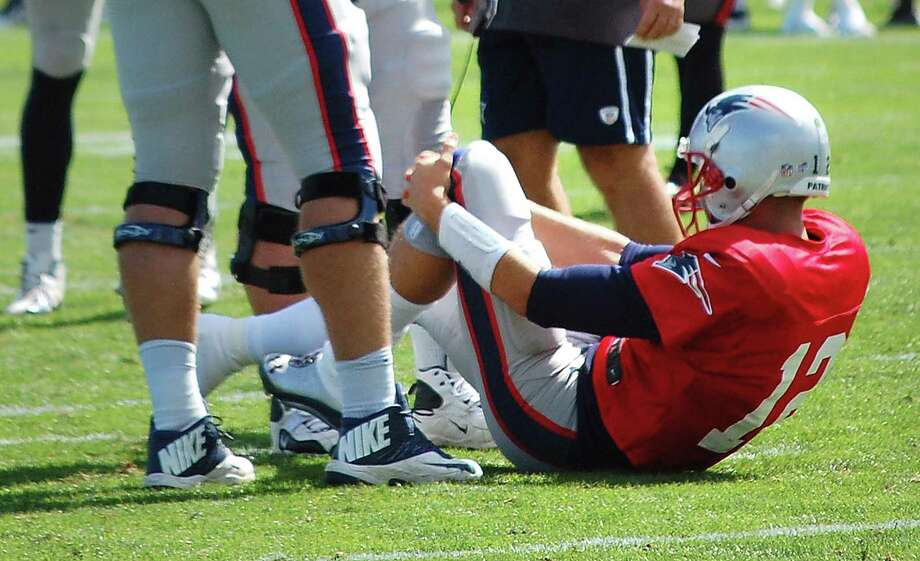 New England Patriots quarterback Tom Brady  grabs his left knee after an apparent injury during a joint workout with the Tampa Bay Buccaneers at NFL football training camp, in Foxborough, Mass., Wednesday, Aug. 14, 2013. (AP Photo/Will DiTullio) Photo: ASSOCIATED PRESS / AP2013
