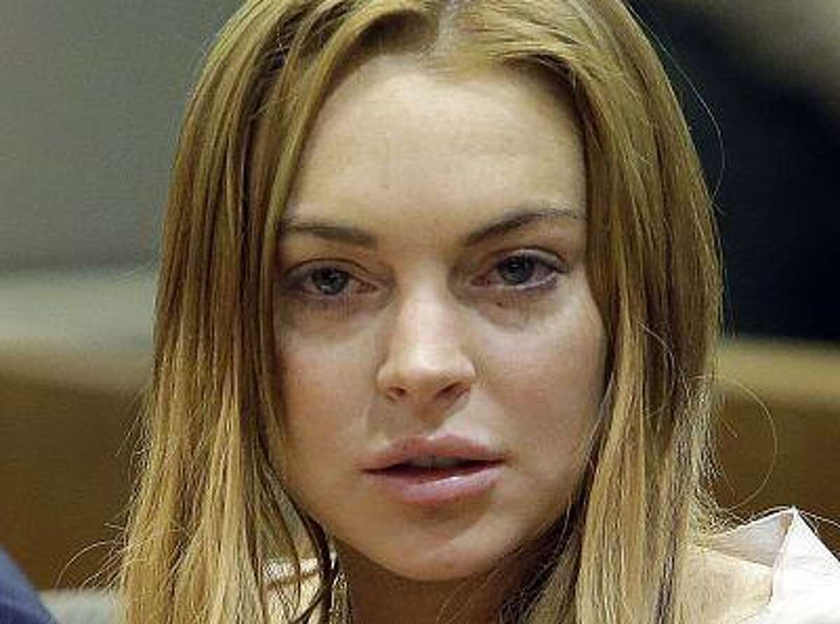 Actress Lindsay Lohan sits at a hearing in Los Angeles Superior Court in Los Angeles, California March 18, 2013. The troubled actress was ordered to spend 90 days in a locked rehabilitation facility and undertake 30 days community labor as part of a plea bargain with prosecutors over charges arising from a June 2012 car crash. REUTERS/Reed Saxon/Pool (UNITED STATES - Tags: ENTERTAINMENT CRIME LAW)