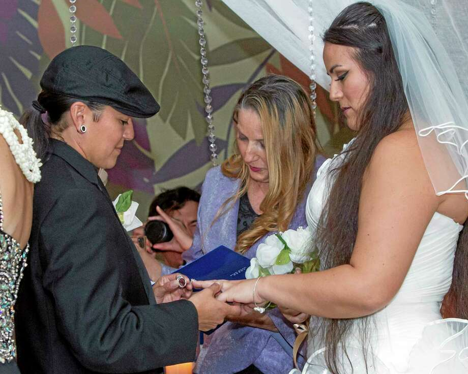 As Rev. Dodi Rose, center, performs the wedding ceremony, Isajah Morales left, places a ring on her partner, Saralyn Morales, during a wedding ceremony at the Sheraton Waikiki, Monday, Dec. 2, 2013 in Honolulu. Hawaii became the 15th state to legalize same-sex marriage Monday, and couples were able to apply for marriage licenses after midnight.  After receiving their marriage license, several couples held a group wedding at the hotel. (AP Photo/Marco Garcia) Photo: AP / FR 132414AP