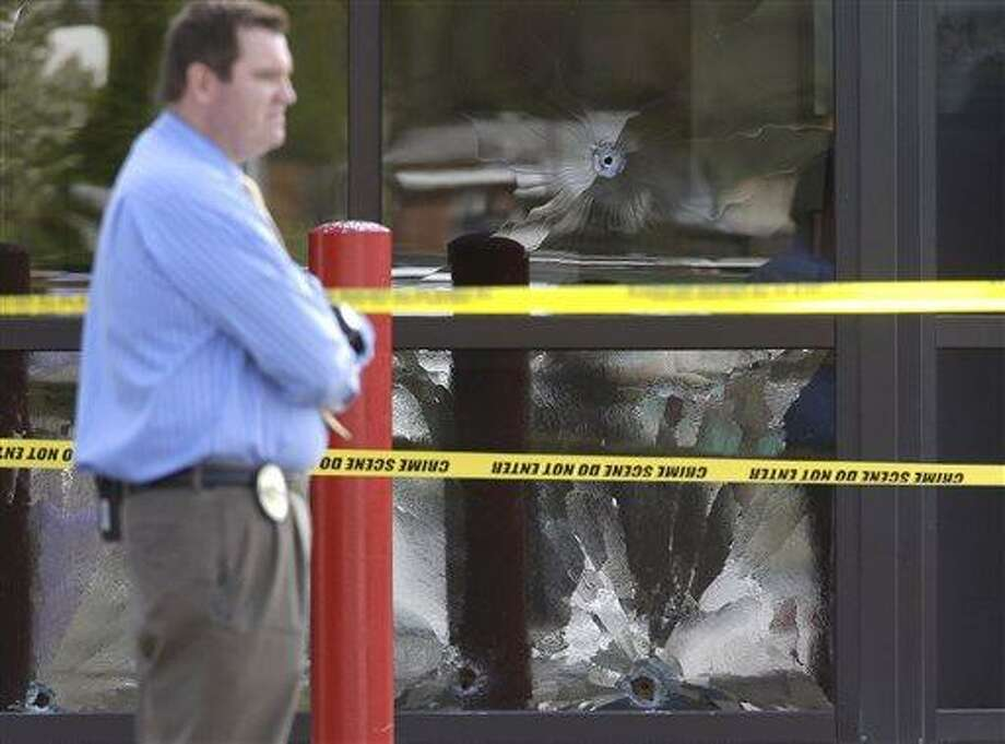 A West Valley City Police Officer stands near a bullet shattered window at the West Valley City Police Department Monday, April 29, 2013, in West Valley City, Utah. Authorities in a Salt Lake City suburb say a man shot after pulling a gun in a police lobby told officers months ago that he wanted to be shot by police. (AP Photo/Rick Bowmer) Photo: AP / AP