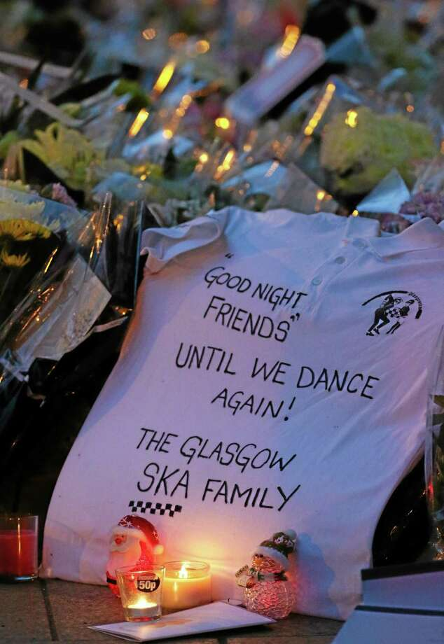 Flowers and messages have been laid out by mourners across from the scene Monday, Dec. 2, 2013, following the helicopter crash at the Clutha Bar in Glasgow, Scotland. Scottish emergency workers were sifting through wreckage over the weekend for survivors of a police helicopter crash onto a crowded Glasgow pub that has killed nine people and injured more than two dozen. The Clutha pub, near the banks of the River Clyde, was packed Friday night and a ska band was in full swing when the chopper slammed through the roof. The number of fatalities is expected to rise, officials said. (AP Photo/Scott Heppell) Photo: AP / AP