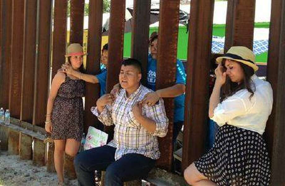 """Evelyn Rivera, left, Carlos Padilla, front center, and Renata Teodoro, right, reunite with their mothers on opposite sides of the border wall that divides Nogales, Arizona from Nogales, Mexico, seen from the U.S. side of the border, Tuesday, June 11, 2013. The youth, who were born in Mexico and brought to the U.S. as children, traveled from Seattle, Miami and Boston to meet at the border fence with their mothers who they had not seen in years. The four are """"dreamers,"""" youth whose families entered the country without authorization when they were children, and through a deferred action plan by President Barack Obama have work permits and protection against deportation. (AP Photo/Valeria Fernandez) Photo: ASSOCIATED PRESS / AP2013"""