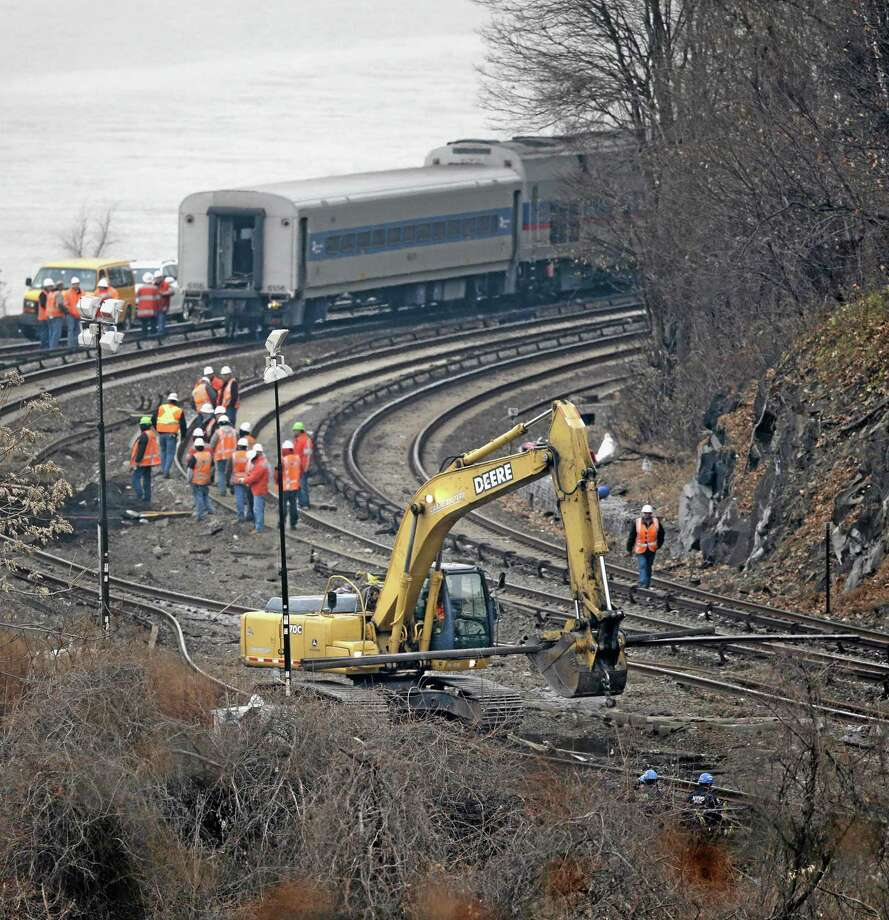 "A construction machine moves a section of railroad track near the site of a train derailment in the Bronx section of New York, Monday, Dec. 2, 2013. Federal authorities began righting the cars Monday morning as they started an exhaustive investigation into what caused a Metro-North commuter train rounding a riverside curve to derail, killing four people and injuring more than 60 others. A second ""event recorder"" retrieved from the train may provide information on the speed of the train, how the brakes were applied, and the throttle setting, a member of the National Transportation Safety Board said Monday. (AP Photo/Seth Wenig) Photo: AP / AP"