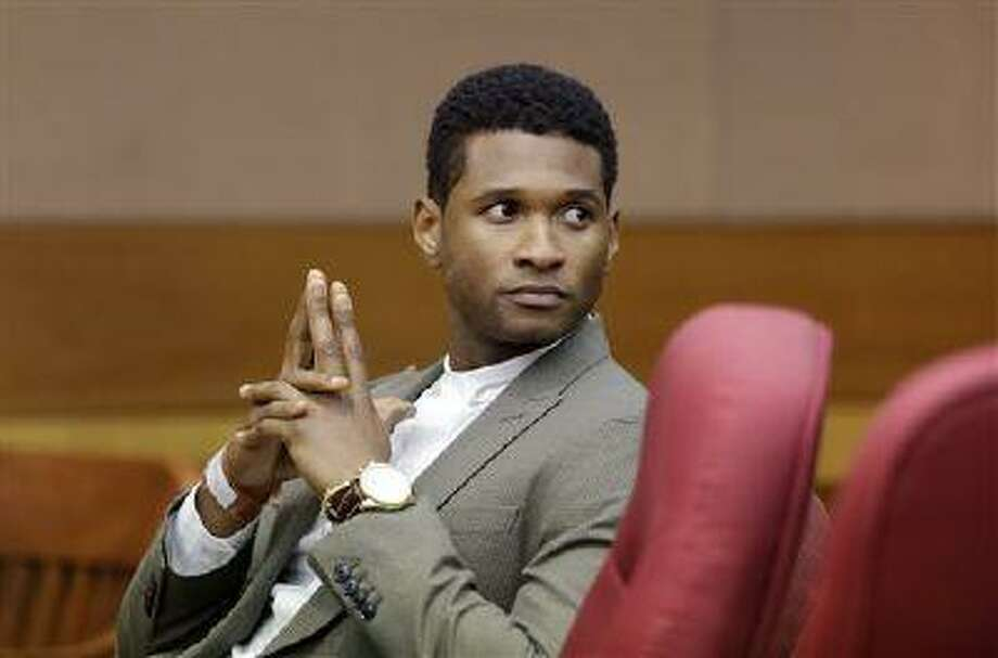 R&B singer Usher waits for a child custody hearing to begin, Friday, Aug. 9, 2013, in Atlanta. A judge in Atlanta is set to hear arguments in the child custody battle between Usher and his ex-wife. Tameka Foster Raymond requested the hearing earlier this week after the former couple's son got caught in a pool drain while in the care of Usher's aunt. (AP Photo/David Goldman) Photo: AP / AP