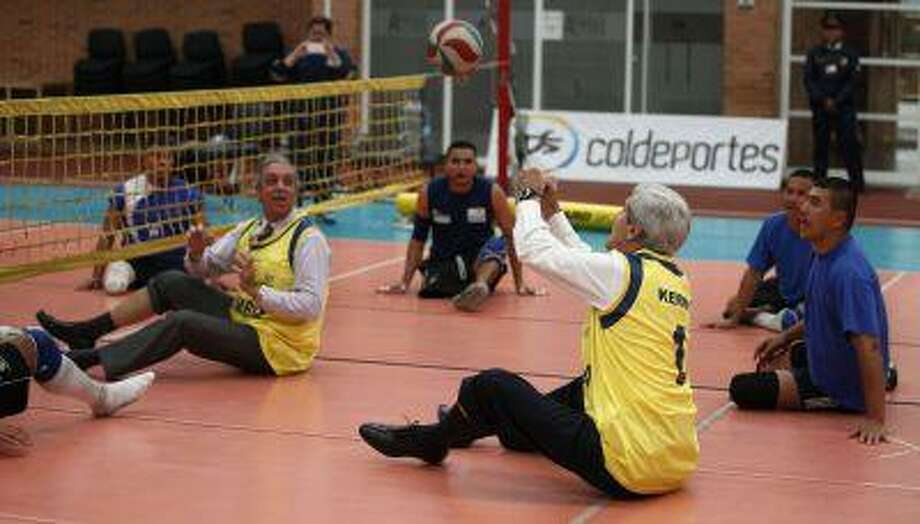 U.S. Secretary of State John Kerry, third from right, plays a volleyball game with handicapped Colombian police officers and Army soldiers who lost their legs in the line of duty during his visit to Bogota, Colombia, Monday, Aug. 12, 2013. Kerry is on a one-day official visit to Colombia. Photo: AP / AP