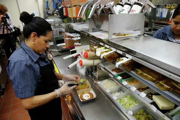 Silvia Ruiz prepares a sandwich at a McDonald's restaurant in Chicago. The chain's revenue fell 3 percent to $6.05 billion, as sales gains at restaurants owned by franchisees were offset by a decline at company-run stores. But its profit rose.